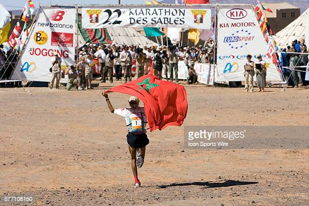 Nine times winner Lahcen Ahansal of Morocco runs to the finish line showing Morocco national banner en route to win the sixth and final stage of the...