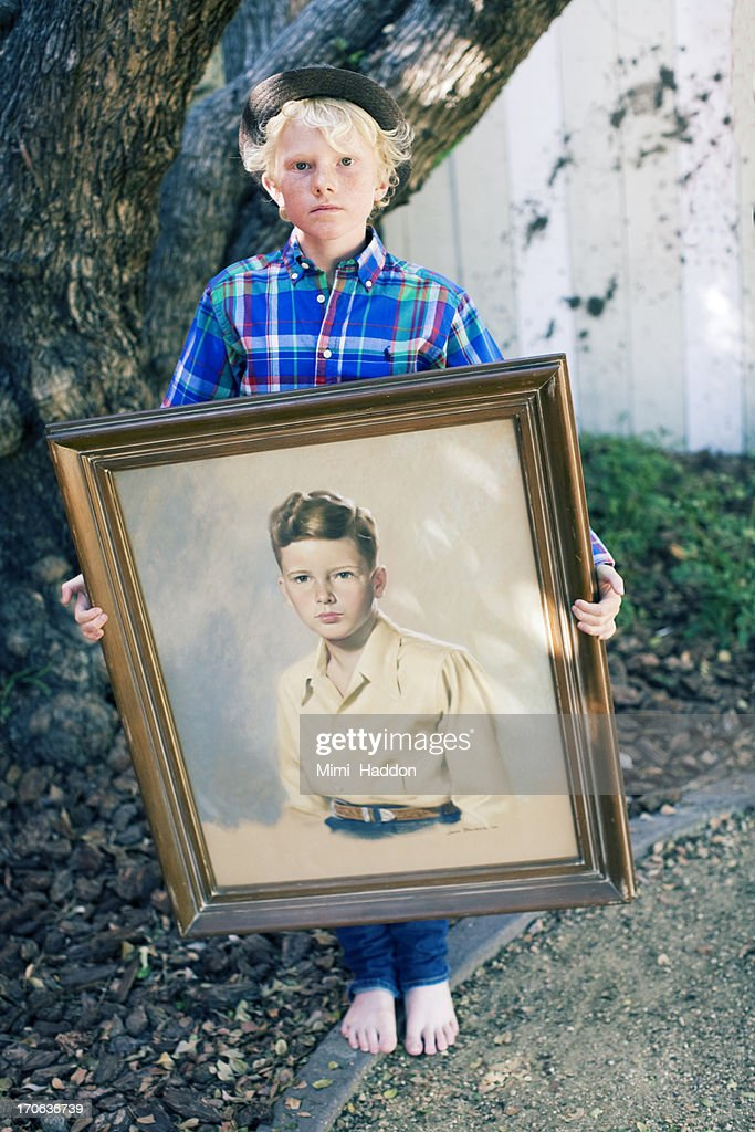Nine Year Old Boy Holding Old Family Portrait : Stock Photo