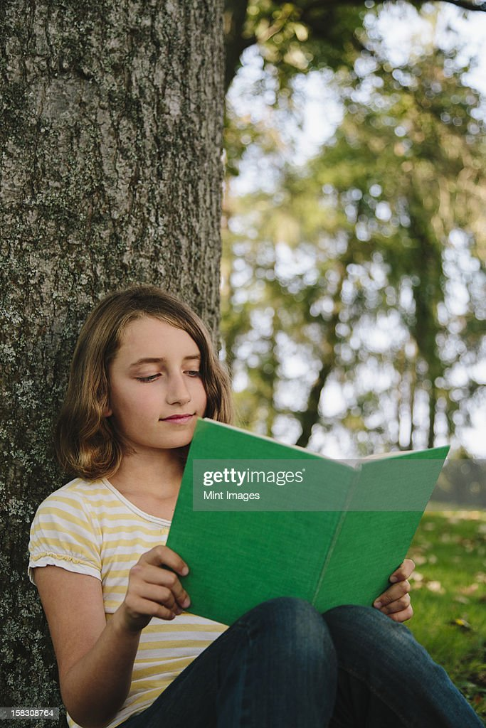 Nine year old girl sitting beneath tree, reading book : Stock Photo