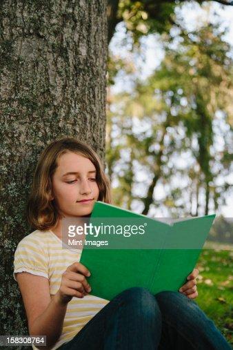 Nueve años Chica bajo el árbol de estar, libro de lectura : Foto de stock