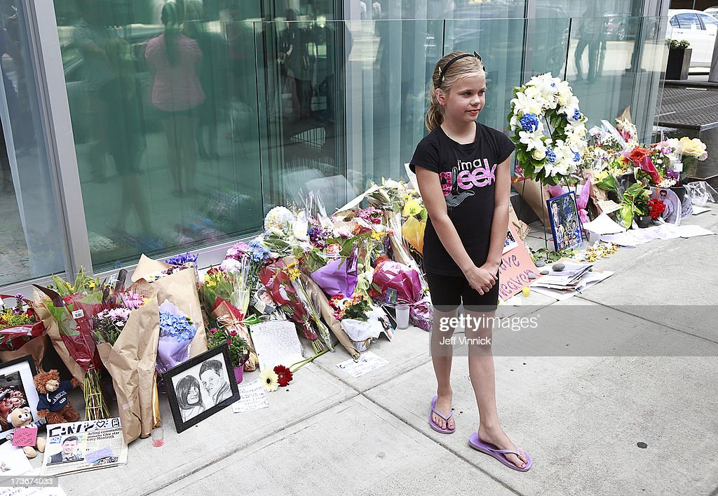 Nine year-old Ava Studiman poses for a photo in front of a memorial to deceased actor Cory Monteith outside the Fairmont Pacific Rim Hotel on July 16, 2013 in Vancouver, British Columbia, Canada. The B.C. Coroners Service released results of Monteith's autopsy today and found the 31-year-old's cause of death was a mixed drug toxicity involving heroin and alcohol..