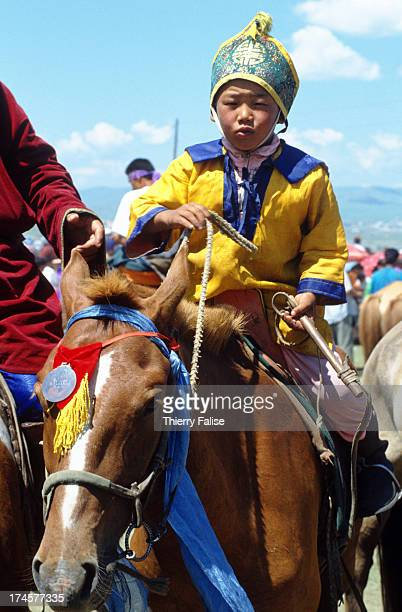 Nine yearold Daransokh one of the winners in the horserace of the Naadam festival poses with his horse Naadam is the national sports festival of...