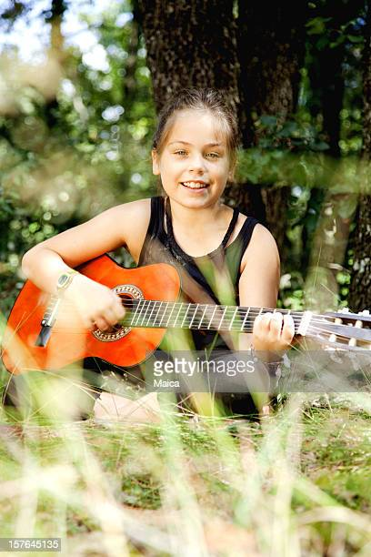 Nine years old playing acoustic guitar outdoors