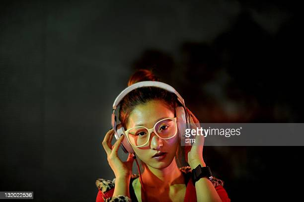 Nineteenyearold Chinese DJ Li Chengxue prepares to start work at a club in Hefei east China's Anhui province on November 8 2011 As the many million...