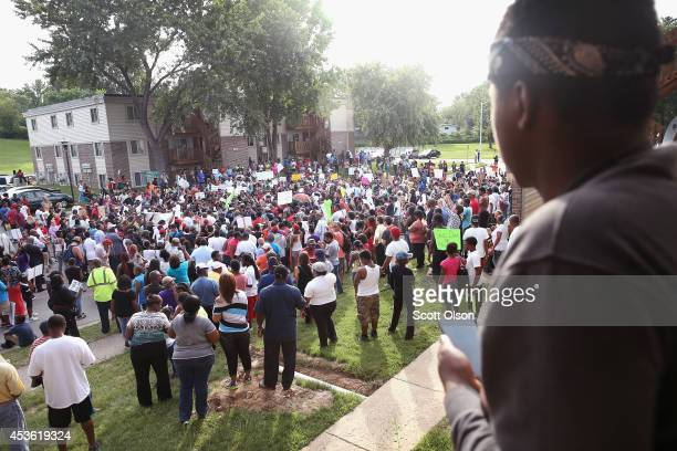 Nineteenyearold Emanuel Freeman looks out from a balcony in his apartment building as demonstators rally in the street where eighteenyearold Michael...