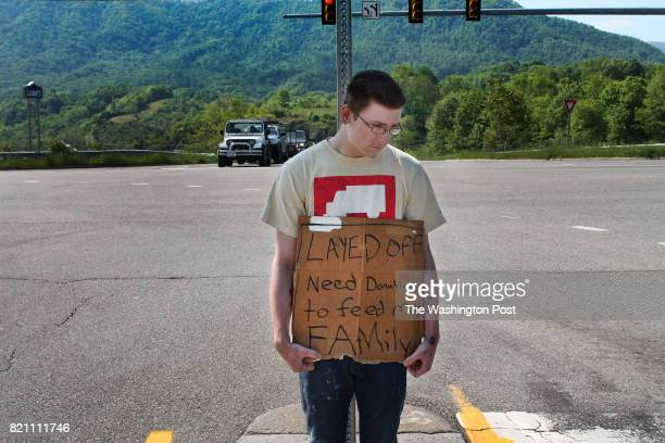 Nineteenyearold Tyler McGlothlin holds a sign seeking monetary donations to feed his family in Richlands VA on May 15 2017 Tyler and his wife live in...