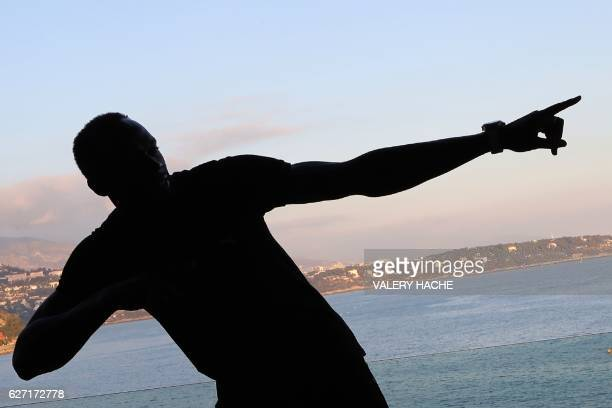 Ninetime Olympic champion Usain Bolt is pictured in silhouette as he poses within the 204th IAAF Council meeting in Monaco on December 2 2016 / AFP /...