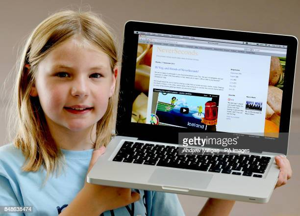 Nineyear old blogger Martha Payne holds a computer with the home page of her blog opened after getting some porridge cooked for her by TV chef Nick...