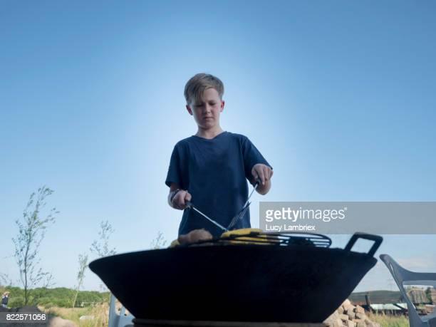 Nine-year-old boy preparing food on the barbecue