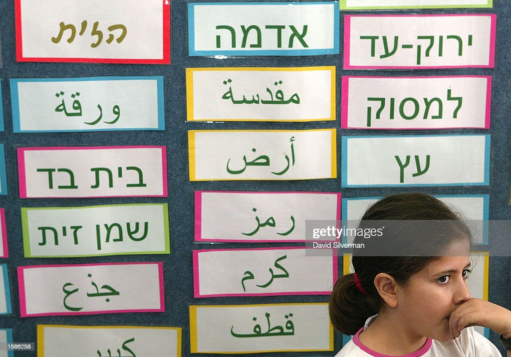 Nineyearold Jewish fourth grade schoolgirl Judith Minski listens to language class at the Bilingual School where both Hebrew and Arabic words adorn...