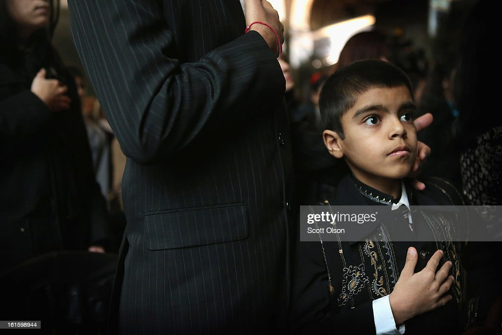 Nine-year-old Mukal Verma from India listens to the National Anthem during a citizenship ceremony at the Chicago Cultural Center on February 12, 2013 in Chicago, Illinois. The ceremony was held to recognize as new U.S. citizens 62 children, ages 6-18, from 23 countries who were adopted from abroad or who derived U.S. citizenship when their immigrant parents were naturalized.