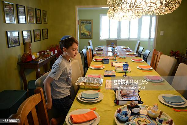 POTOMAC MD Nineyearold Remy Eidelman looks at the table decoration for the upcoming Seder dinner at this family home in Potomac MD April 2 2015 Remy...