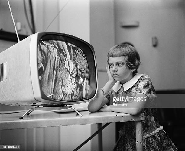 Nineyearold Rosemary Muller of Roslyn Heights Long Island recovering from a heart operation watches a similar operation being performed on television...