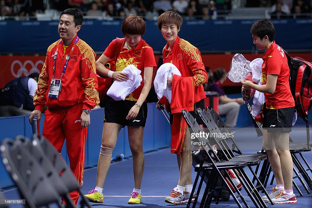 Ning Ding, <a gi-track='captionPersonalityLinkClicked' href=/galleries/search?phrase=Xiaoxia+Li+-+Table+Tennis+Player&family=editorial&specificpeople=4049514 ng-click='$event.stopPropagation()'>Xiaoxia Li</a> and Yue Guo of China leave with their coach Zhihao Shi during Women's Team Table Tennis first round match against team of Spain on Day 7 of the London 2012 Olympic Games at ExCeL on August 3, 2012 in London, England.