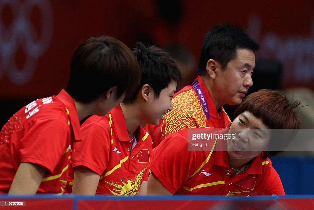 Ning Ding, <a gi-track='captionPersonalityLinkClicked' href=/galleries/search?phrase=Xiaoxia+Li+-+Table+Tennis+Player&family=editorial&specificpeople=4049514 ng-click='$event.stopPropagation()'>Xiaoxia Li</a> and Yue Guo of China speaks beside their coach Zhihao Shi during Women's Team Table Tennis first round match against team of Spain on Day 7 of the London 2012 Olympic Games at ExCeL on August 3, 2012 in London, England.