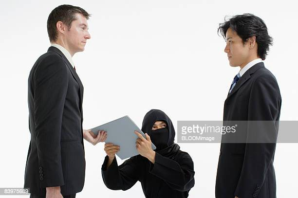 Ninja bringing documents to businessman, studio shot