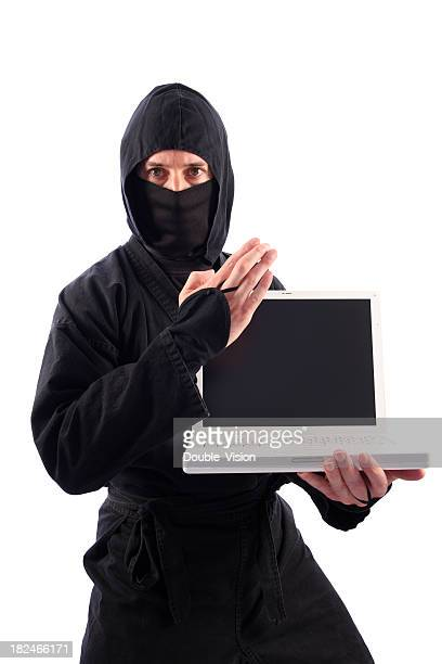 Ninja in Black Guarding Laptop Computer with Knife-Hand Technique
