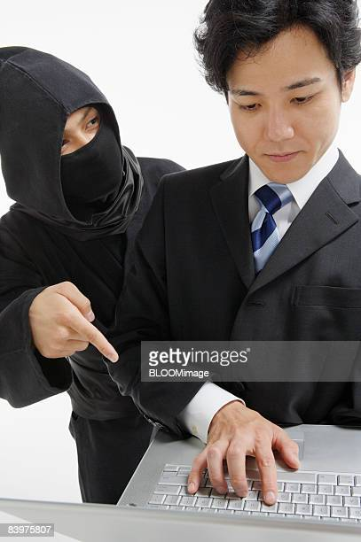 Ninja pointing at businessman's laptop PC, studio shot