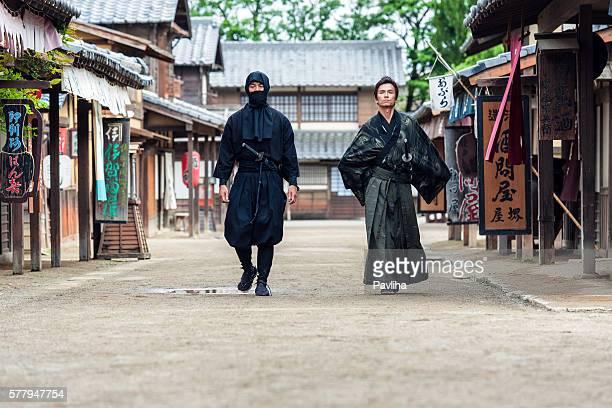 Ninja, samurais de marche au milieu de la rue du village