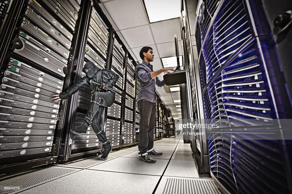 Ninja sneaking past sever room employee : Stock Photo