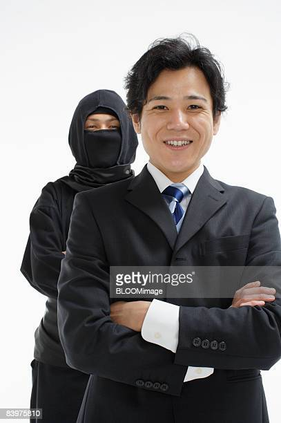 Ninja standing behind businessman, studio shot