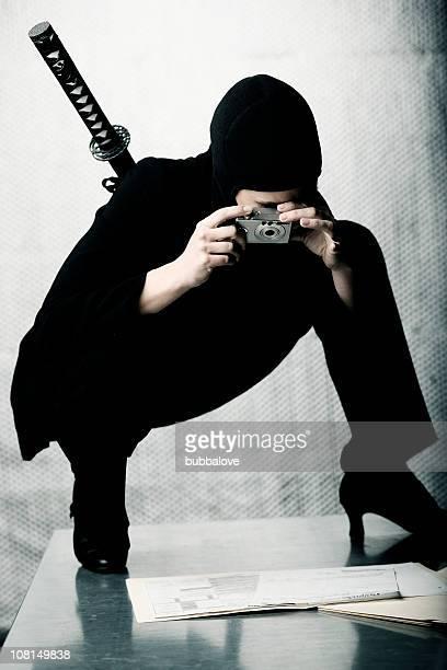 Ninja Frau stehend auf Tisch und Fotografieren Dokumente
