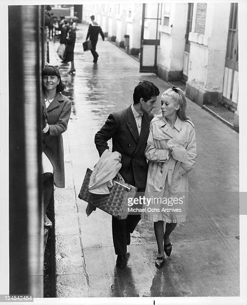 Nino Castelnuovo and Catherine Deneuve walk down a wet sidewalk in a scene from the film 'The Umbrellas Of Cherbourg' 1964