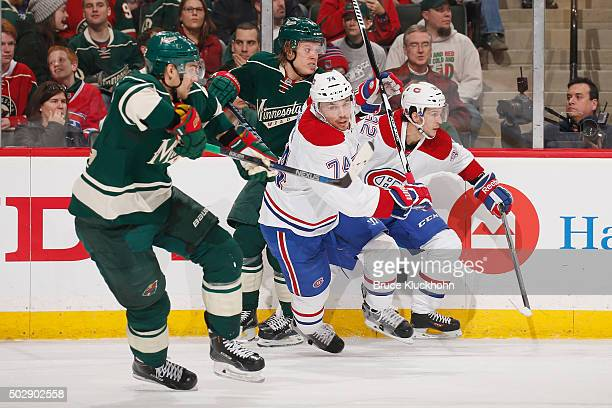 Nino Niederreiter and Mikael Granlund of the Minnesota Wild skate to the puck against Alexei Emelin and Brian Flynn of the Montreal Canadiens during...
