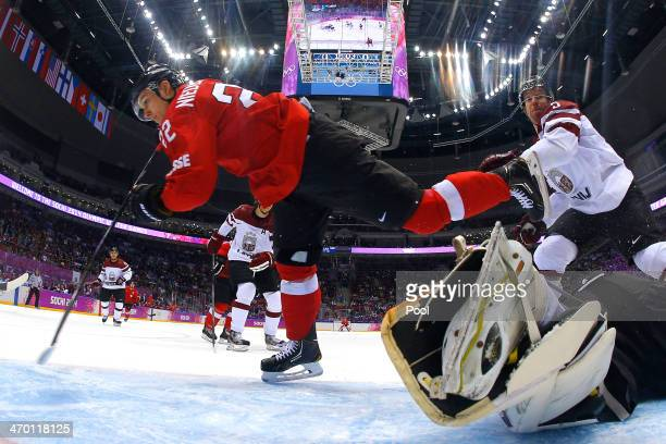 Nino Niederreiter of Switzerland falls to the ice against Edgars Masalskis of Latvia in the first period during the Men's Ice Hockey Qualification...