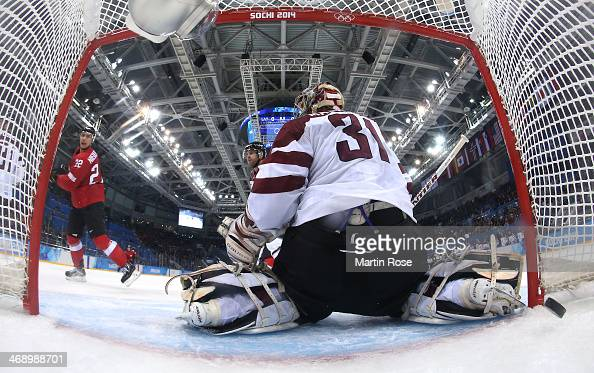 Nino Niederreiter of Switzerland scores a goal late in the third period against Edgars Masalskis of Latvia during the Men's Ice Hockey Preliminary...
