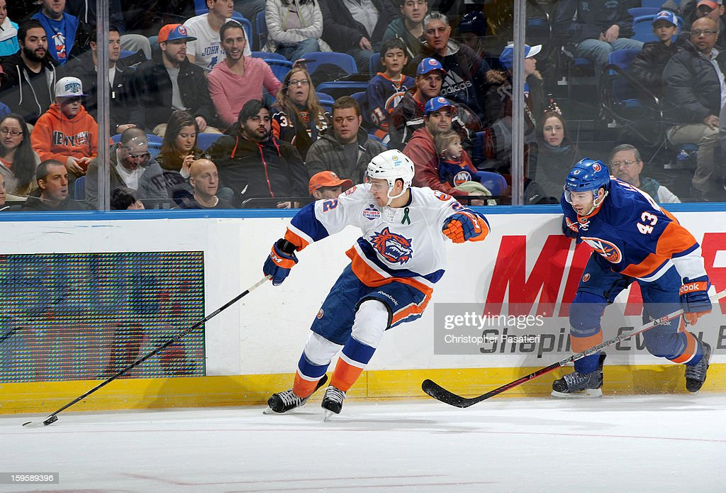 Nino Niederreiter #22 of Team White reaches for the puck against Jon Landry #43 of Team Blue during a scrimmage match between players of the New York Islanders and Bridgeport Sound Tigers on January 16, 2013 at Nassau Veterans Memorial Coliseum in Uniondale, New York.