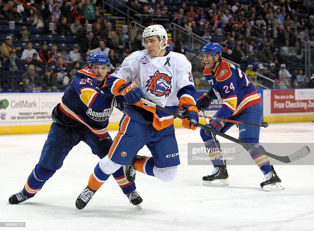 Nino Niederreiter #22 of the Bridgeport Sound Tigers is cross checked by Matt Smaby #25 of the Norfolk Admirals during an American Hockey League on February 2, 2013 at the Webster Bank Arena at Harbor Yard in Bridgeport, Connecticut.