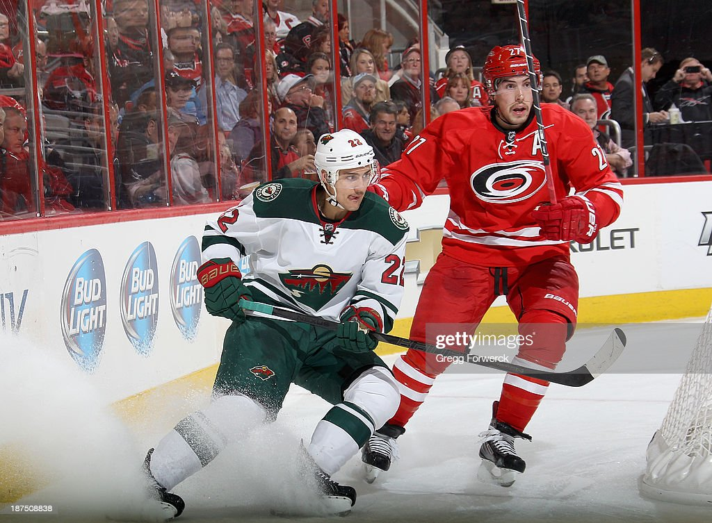 Nino Niederreiter #22 of the Minnesota Wild and Justin Faulk #27 of the Carolina Hurricanes skate behind the net during their NHL game at PNC Arena on November 9, 2013 in Raleigh, North Carolina.