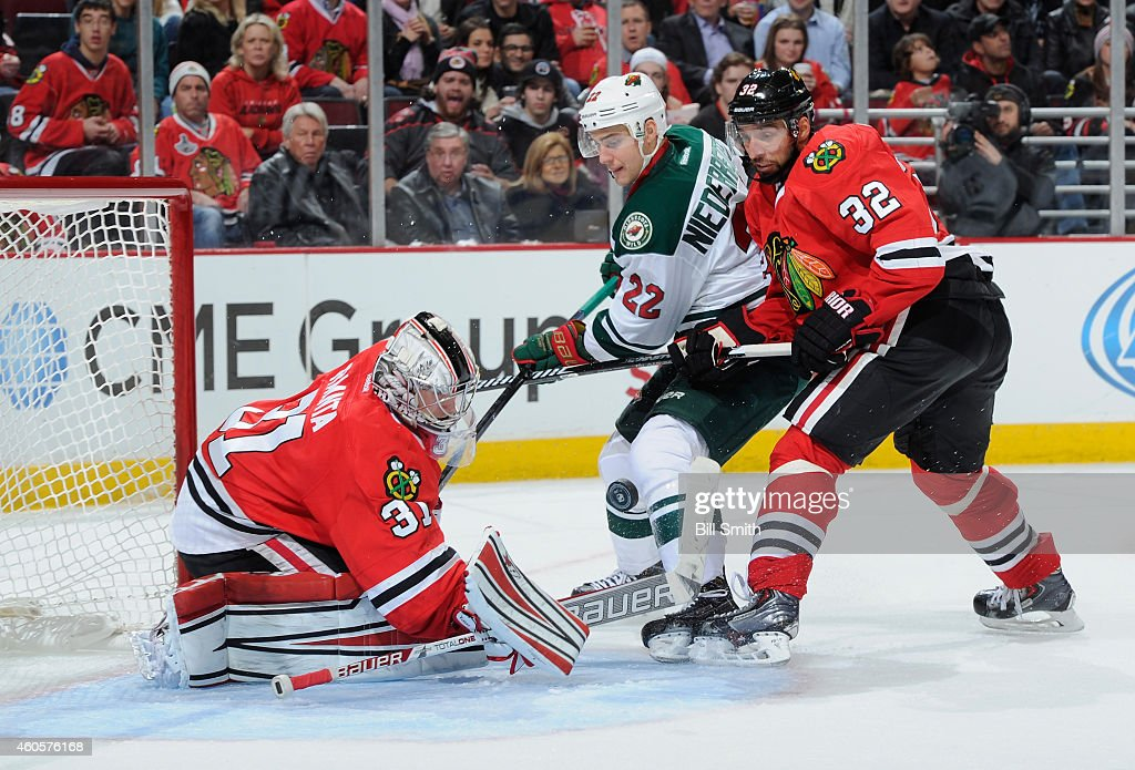 Nino Niederreiter of the Minnesota Wild and Michal Rozsival of the Chicago Blackhawks approach the puck as it flies toward goalie Antti Raanta during...