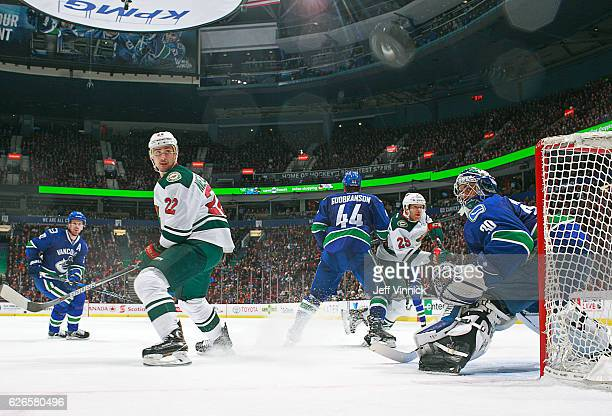 Nino Niederreiter of the Minnesota Wild and Ryan Miller of the Vancouver Canucks watch a shot go past the net during their NHL game at Rogers Arena...