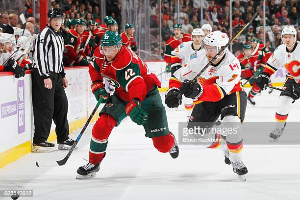 Nino Niederreiter of the Minnesota Wild and TJ Brodie of the Calgary Flames skate to the puck during the game on November 15 2016 at the Xcel Energy...