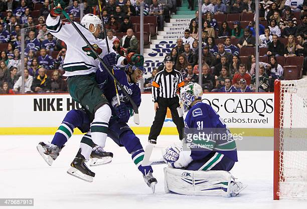 Nino Niederreiter of the Minnesota Wild collides with Chris Tanev of the Vancouver Canucks in front of goaltender Eddie Lack during the first period...
