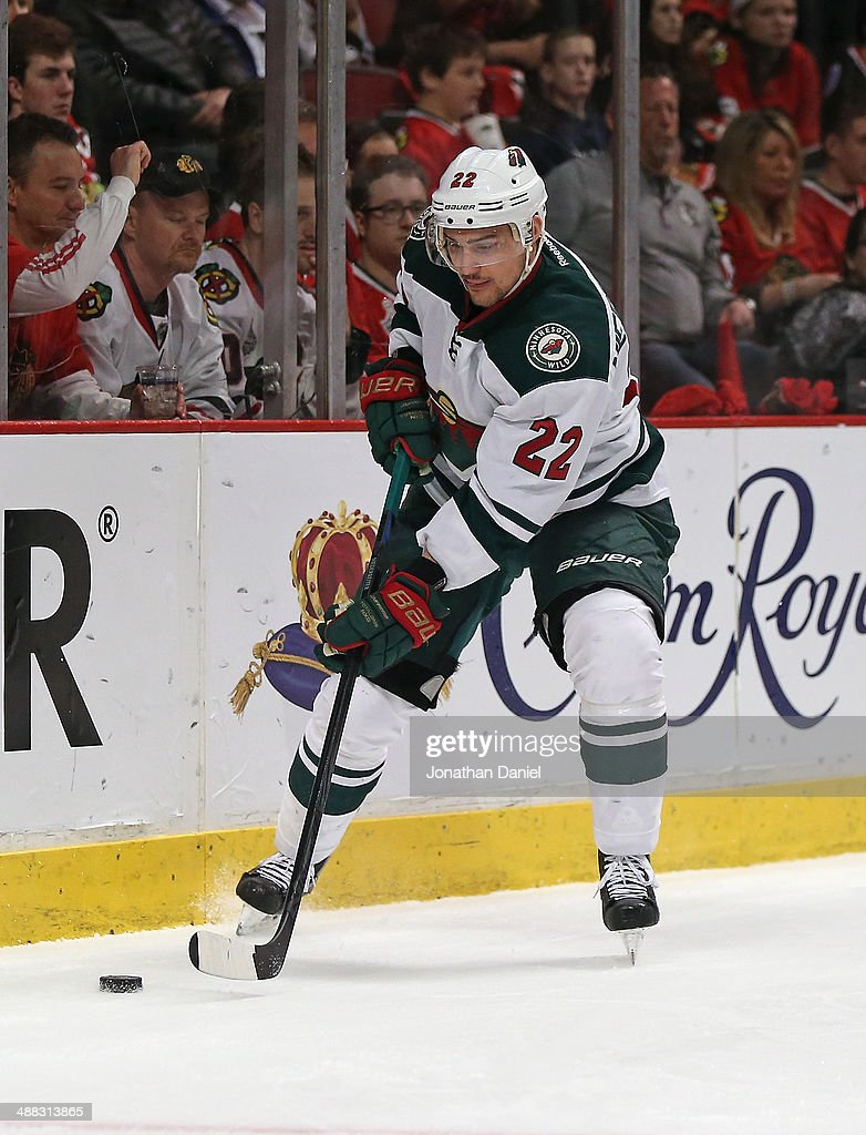 Nino Niederreiter of the Minnesota Wild controls the puck against the Chicago Blackhawks closes in during Game Two of the Second Round of the 2014...