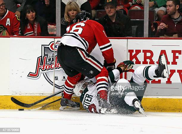 Nino Niederreiter of the Minnesota Wild hits the ice as he battles for the puck with Marcus Kruger of the Chicago Blackhawks in Game One of the...