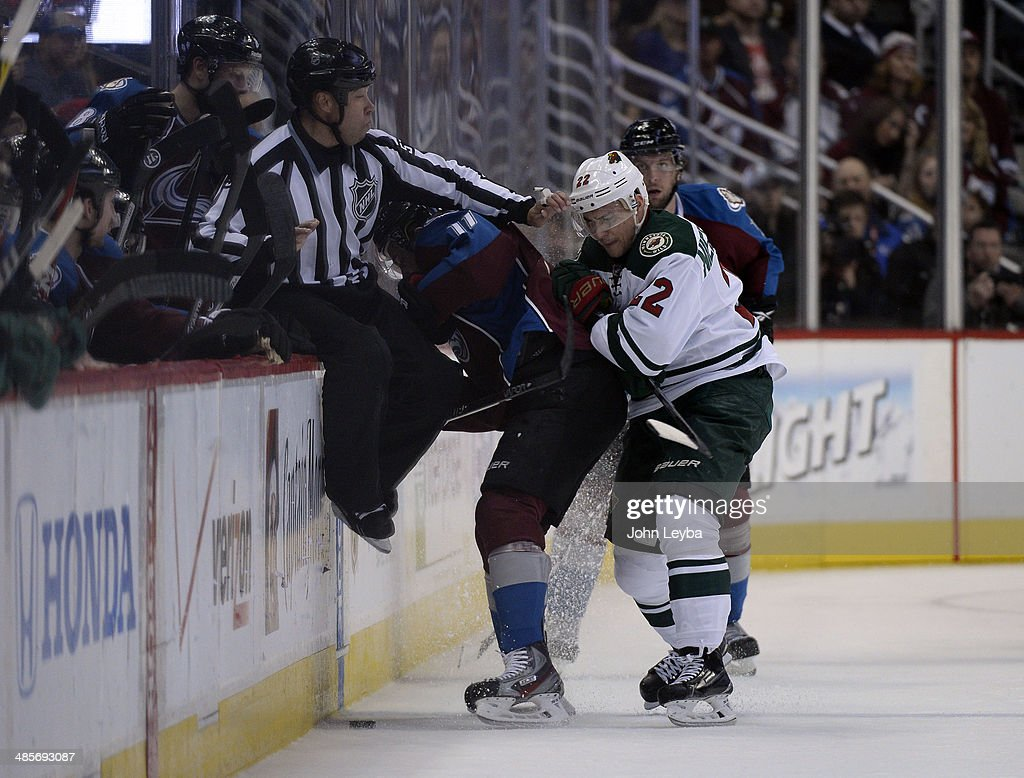 Nino Niederreiter (22) of the Minnesota Wild pushes Jamie McGinn (11) of the Colorado Avalanche into the bench during the first period of action. linesman Jay Sharrers (57) gets caught in the action. The Colorado Avalanche hosted the Minnesota Wild in the first round of the Stanley Cup Playoffs at the Pepsi Center in Denver, Colorado on Saturday, April 19, 2014.