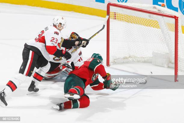 Nino Niederreiter of the Minnesota Wild scores a goal against Jyrki Jokipakka and goalie Craig Anderson of the Ottawa Senators during the game on...