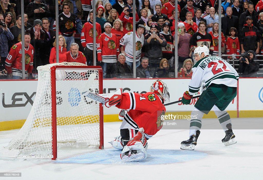 Nino Niederreiter #22 of the Minnesota Wild scores a penalty shot on goalie Antti Raanta #31 of the Chicago Blackhawks in the third period of the NHL game at the United Center on December 16, 2014 in Chicago, Illinois.