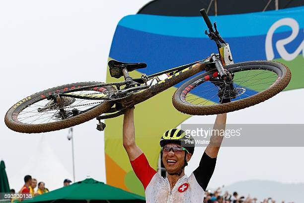 Nino Schurter of Switzerland celebrates winning gold during the Men's CrossCountry on Day 16 of the Rio 2016 Olympic Games at Mountain Bike Centre on...