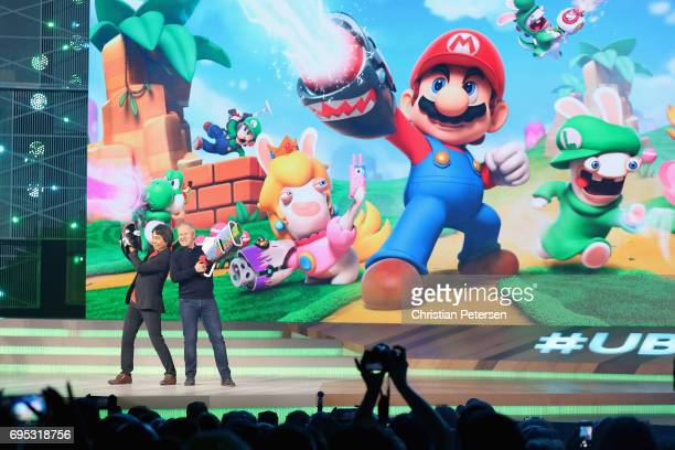 Nintendo coRepresentative Director and Creative Fellow Shigeru Miyamoto and Ubisoft Cofounder and CEO Yves Guillemot pose together on stage during...