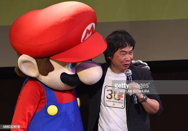 Nintendo's game creator Shigeru Miyamoto poses with his character 'Super Mario' during a live performance of the most wellknown Mario music to mark...