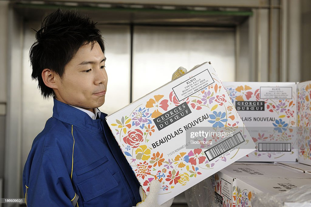 A Nippon Express Co. employee carries a box of Beaujolais Nouveau wine at Haneda Airport in Tokyo, Japan, on Tuesday, Nov. 5, 2013. Japanese appetite for Beaujolais Nouveau has made the country the largest buyer of the young wine outside France, purchasing three times the U.S., the next biggest importer. Photographer: Akio Kon/Bloomberg via Getty Images