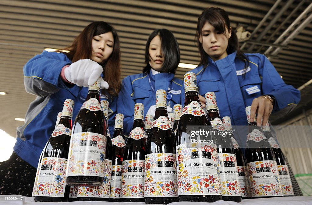 Nippon Express Co. employees arrange bottles of Georges Duboeuf Beaujolais Nouveau wine at Haneda Airport in Tokyo, Japan, on Tuesday, Nov. 5, 2013. Japanese appetite for Beaujolais Nouveau has made the country the largest buyer of the young wine outside France, purchasing three times the U.S., the next biggest importer. Photographer: Akio Kon/Bloomberg via Getty Images
