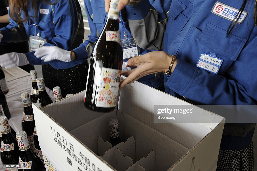 Nippon Express Co. employees open boxes of Georges Duboeuf Beaujolais Nouveau wine at Haneda Airport from the storage space of passenger-plane bellies at Haneda Airport in Tokyo, Japan, on Tuesday, Nov. 5, 2013. Japanese appetite for Beaujolais Nouveau has made the country the largest buyer of the young wine outside France, purchasing three times the U.S., the next biggest importer. Photographer: Akio Kon/Bloomberg via Getty Images