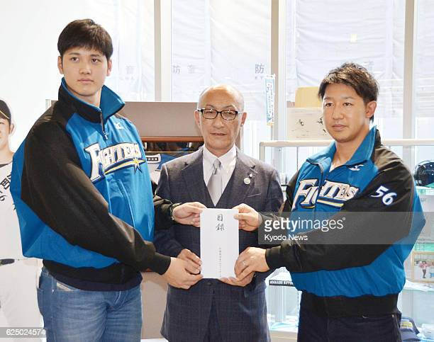 Nippon Ham Fighters pitcher Shohei Otani and catcher Tomoya Ichikawa hand over a list of donations for relief work in Makubetsu Hokkaido which was...