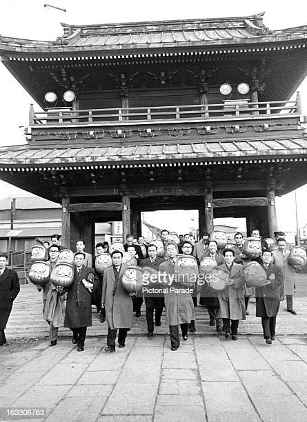 Nippon Kokan representatives carry 20 large Daruma dolls to be offered to the Kawasaki Daishi Shrine in thanks for the plant safety record Japan 1963